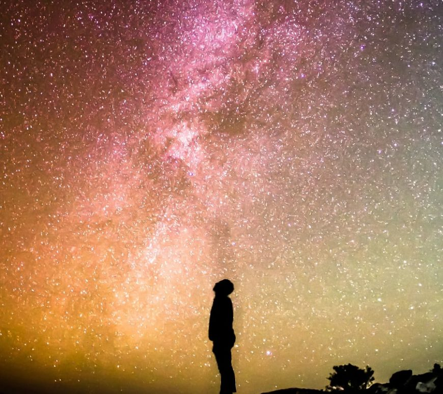 We see a photo of the night sky with the Milky Way clearly visible. A silhouette of a person is standing at the centre, on the floor. The person is looking up.