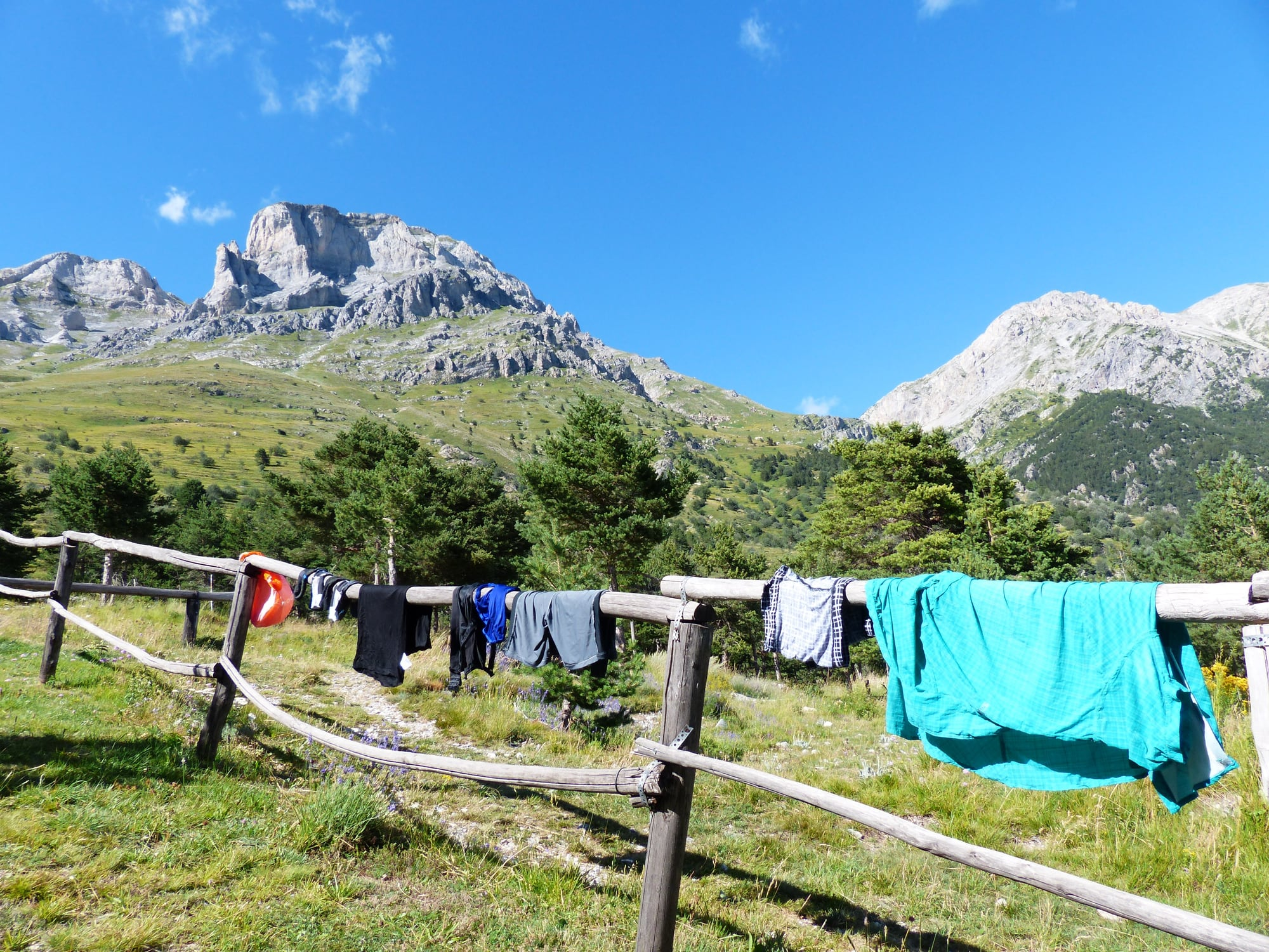 Clothes hang out to dry against a backdrop of mountains